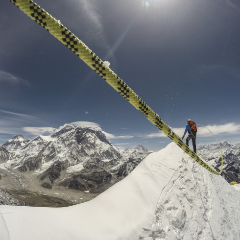 A sherpa climbing up Mount Everest with a rope.